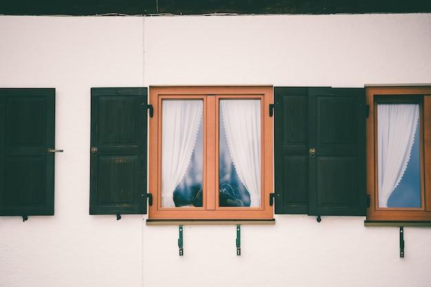 Ventana de vidrio con marco de madera y una cortina blanca en el interior.