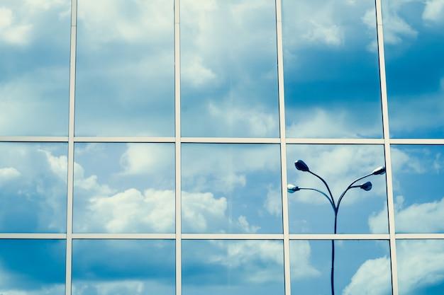 Ventanas con espejos, reflejo de nubes y linterna, cielo azul, superficie de rascacielos. patrón de línea, perspectiva, estructura de acero, abstracción urbana. forma geométrica, exterior moderno, textura de la pared.