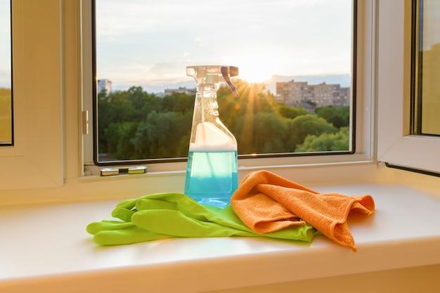 Ventanas limpiadas, guantes protectores de goma, trapo y detergente pulverizador.