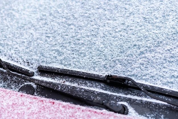 Ventanilla de coche cubierta de nieve con limpiaparabrisas
