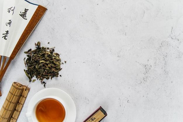 Ventilador asiático tradicional con té de hierbas y mantel enrollado sobre fondo de hormigón