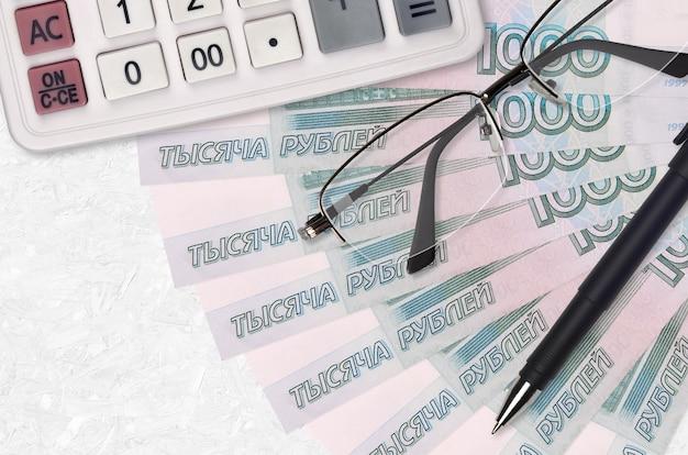 Ventilador de billetes de 1000 rublos rusos y calculadora con gafas y bolígrafo