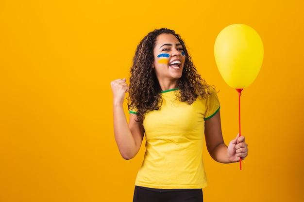 Ventilador brasileño sosteniendo un globo amarillo con espacio libre para texto. promoción de juegos de brasil