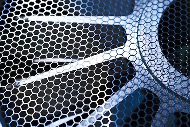 Ventilador industrial de malla metálica protectora. agujeros hexagonales de rejilla. disparo macro, luz oscura, mala iluminación,
