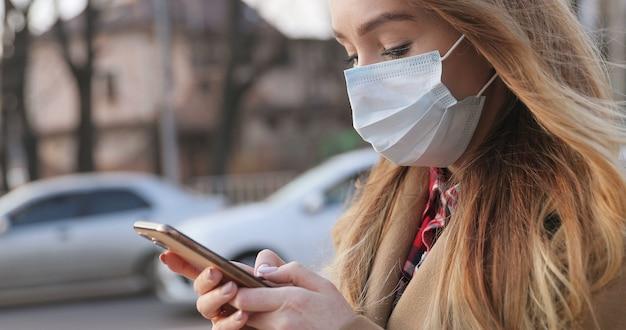 Ver desde abajo en la hermosa joven caucásica en máscara médica usando su teléfono inteligente al aire libre. mensaje de texto de niña bonita y página de noticias de desplazamiento en el teléfono durante la pandemia en la calle.