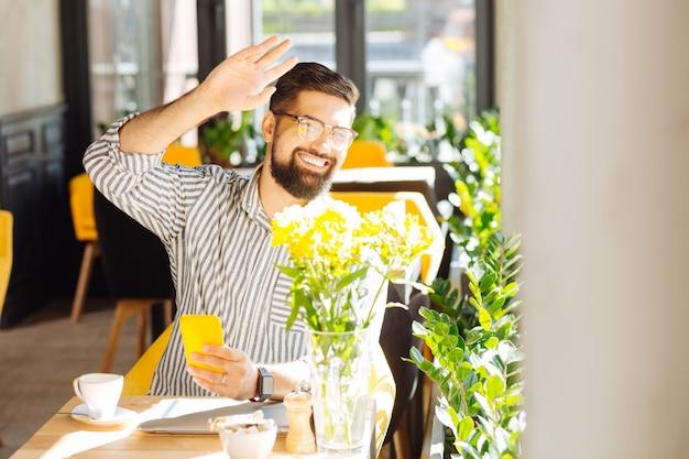 Ver a un amigo. hombre feliz alegre sosteniendo su mano mientras ve a su amigo en la ventana