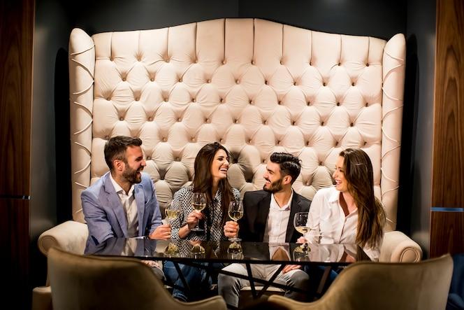 Ver en el alegre grupo de jóvenes brindando con vino blanco