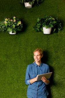 Ver en mujer joven posando con tableta por pared verde
