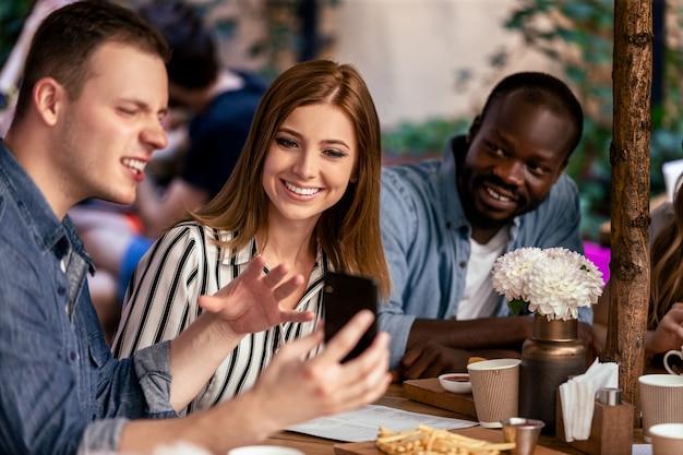 Ver fotos divertidas en el teléfono inteligente en la reunión informal informal con amigos cercanos