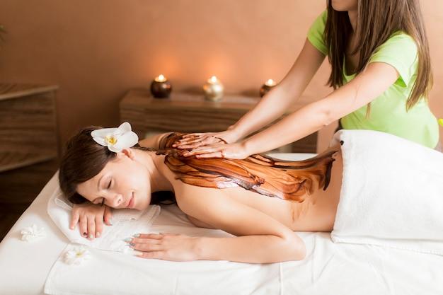 Ver a la mujer teniendo un masaje de chocolate caliente.