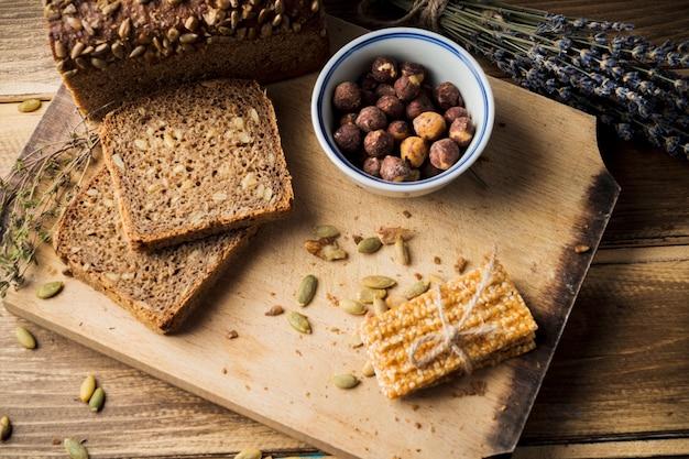Para ver el pan orgánico fresco con ingredientes y barra de energía en la tabla de cortar