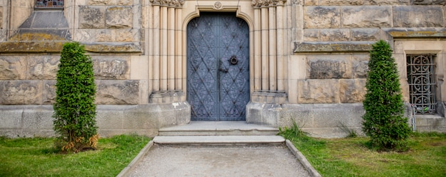 Ver en la puerta vintage y el frente del castillo desde un patio