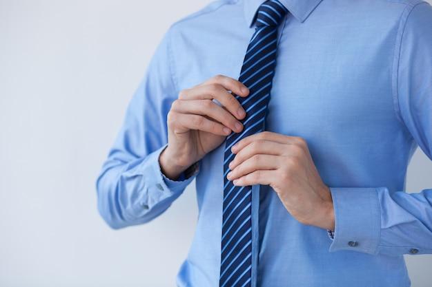 Ver recortada de líder de negocios que ajusta el lazo