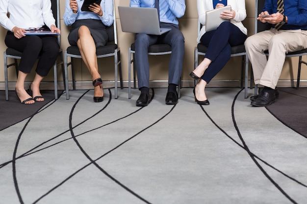 Ver recortada de negocios que se sientan en fila