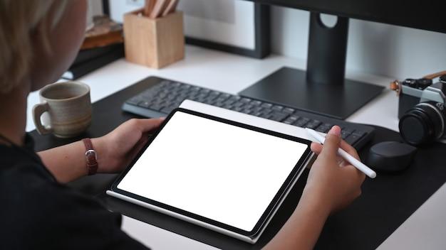 Ver sobre el hombro de la mujer joven sosteniendo simulacros de tableta digital con pantalla en blanco en la oficina.