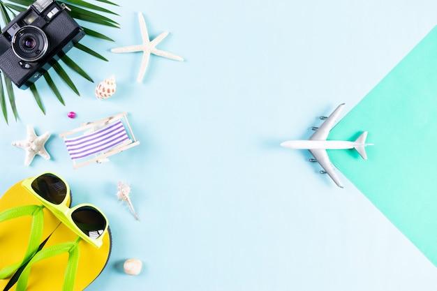 Verano, accesorios de playa, cámara, avión, gafas de sol, flip flop estrella de mar sobre fondo azul pastel.