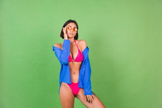 Verano ajuste mujer deportiva en bikini rosa, camisa azul y gafas de sol naranjas en verde, feliz alegre alegre positivo
