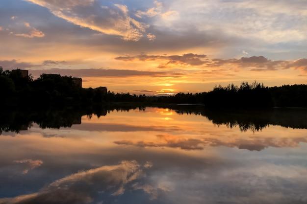 Verano colorido atardecer en el lago con nubes reflejadas en el agua