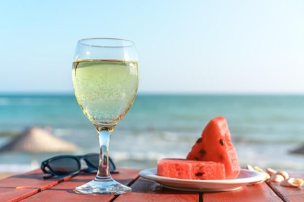 Verano, una copa de champán y fruta contra el fondo del mar.