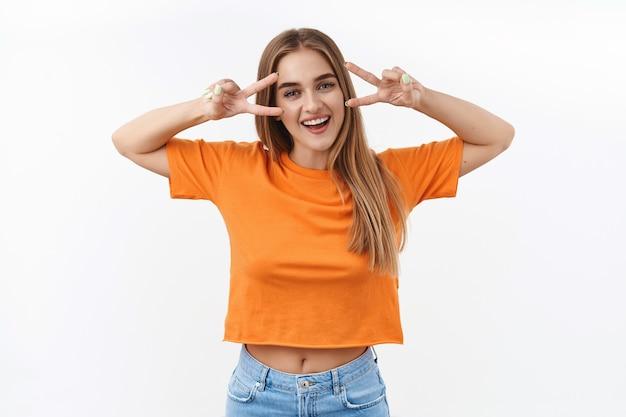 Verano, estudiantes y concepto de juventud. retrato de alegre chica rubia enviando vibraciones positivas