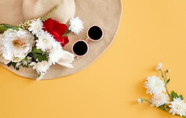 Verano con flores blancas y un sombrero de mimbre con gafas de sol