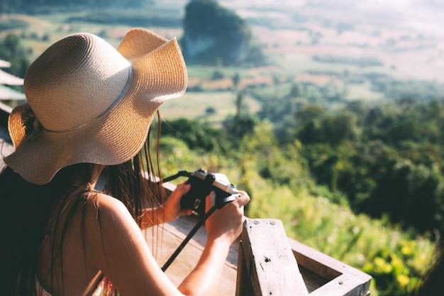 Verano hermosa chica sosteniendo una cámara con vista a la montaña