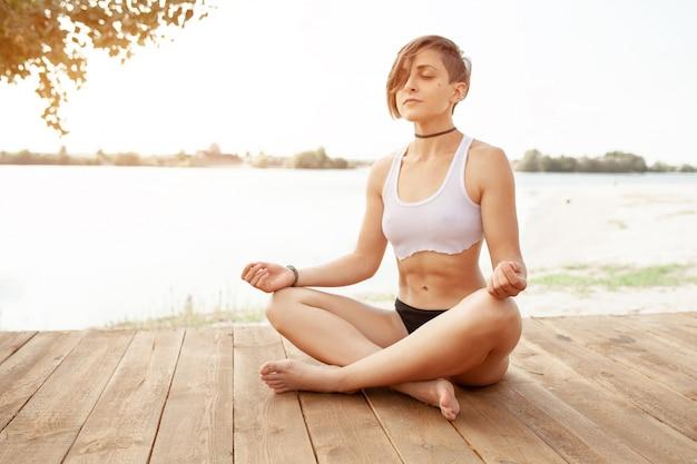 Verano. una hermosa niña con un corte de pelo corto practica yoga.