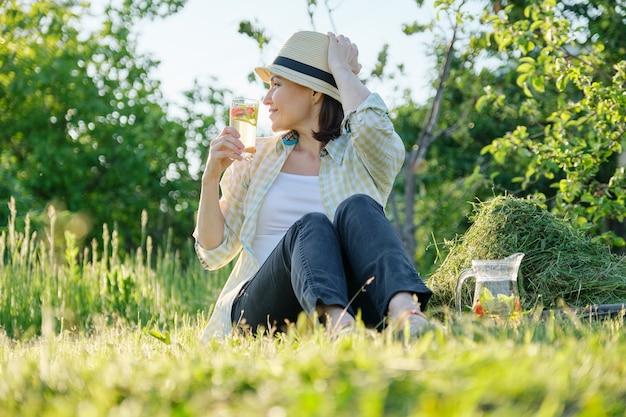 El verano, el jardinero de la mujer con sombrero sentado sobre la hierba recién cortada con menta bebida natural casera con fresas, fondo de jardín verde