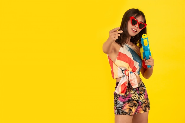 Verano joven bella mujer con pistola de agua, vacaciones songkran