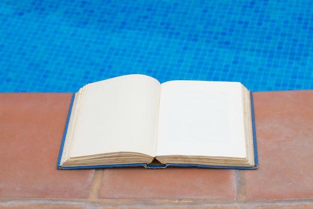 Verano leyendo libro vacío abierto al lado de la piscina