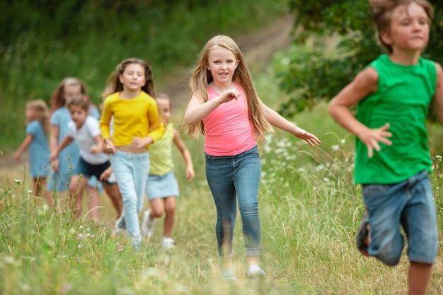 Verano. niños, niños corriendo en bosque verde.
