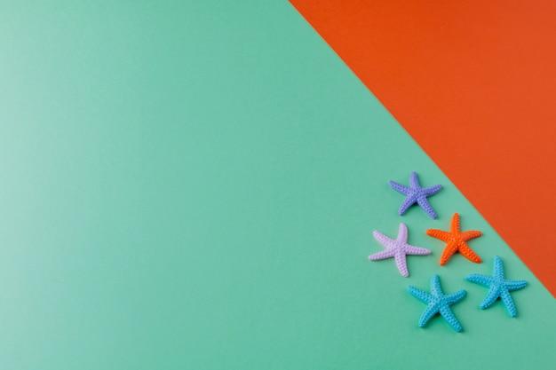 Verano de papel verde y naranja con pequeñas estrellas de mar de colores. vacaciones de verano y viajes planos. copyspace