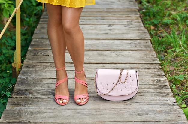 Verano piernas de una joven con un hermoso bronceado en sandalias con tacones junto al bolso de una dama.