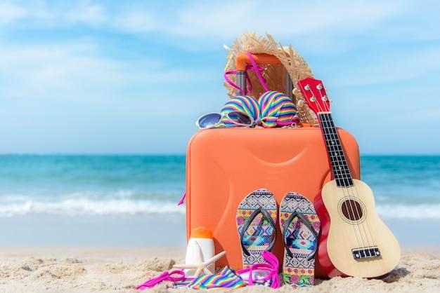 Verano viajando con maleta vieja y traje de baño de mujer de moda bikini, estrella de mar, gafas de sol, sombrero. viajar en las vacaciones, puesta de sol playa de fondo. concepto de verano y viajes.