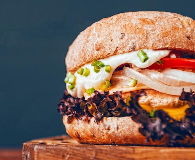 Una verdadera hamburguesa sobre un fondo de madera. con una chuleta grande y jugosa, salsa de queso tierno y mostaza. con lugar para texto