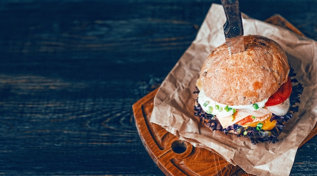 Una verdadera hamburguesa sobre un fondo de madera. con una chuleta grande y jugosa, salsa de queso tierno y mostaza. rústico