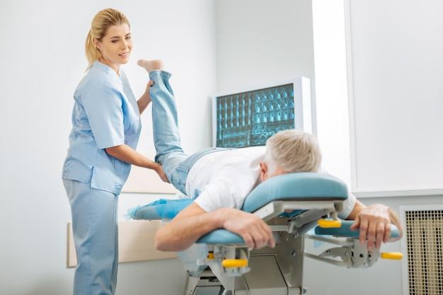 Verdadero especialista. agradable y agradable médico hábil de pie cerca de su paciente y sosteniendo su pierna mientras se concentra en su trabajo