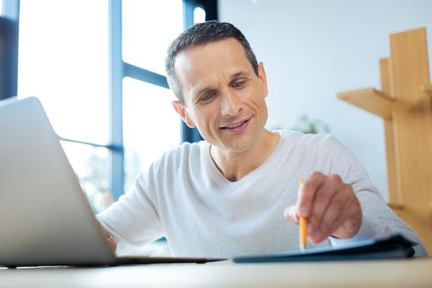 Verdadero profesional. gerente agradable trabajador alegre sentado en la mesa y trabajando con los documentos mientras está en la oficina