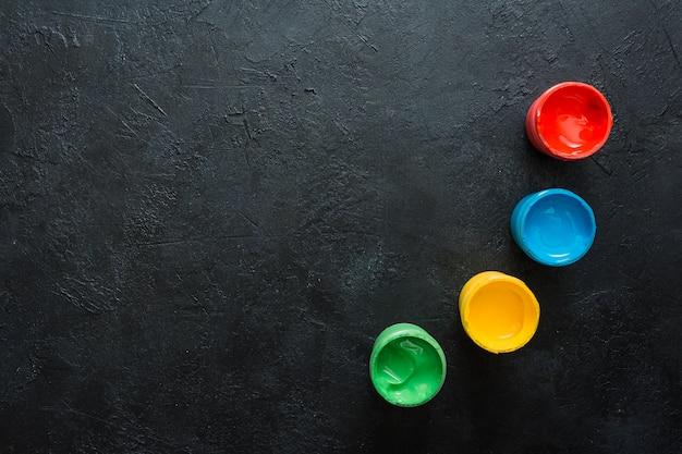 Verde; amarillo; recipiente de pintura pequeña rojo y azul en superficie de pizarra