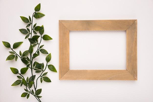 Un verde artificial deja cerca del marco rectangular de madera sobre fondo blanco.