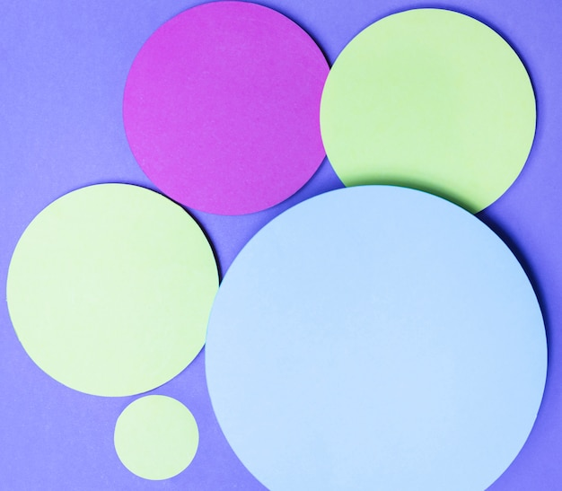 Verde; los círculos de papel de color rosa y gris enmarcan el texto sobre fondo púrpura