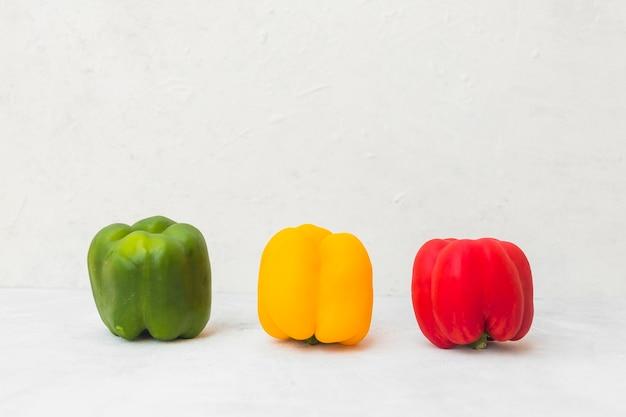 Verde; pimientos amarillos y rojos en superficie blanca