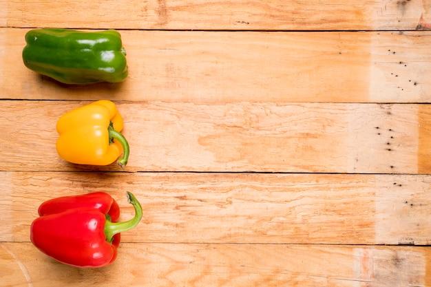 Verde; pimientos rojos y amarillos en tablón de madera