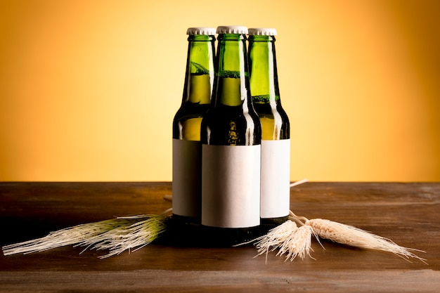Verdes botellas de alcohol en mesa de madera
