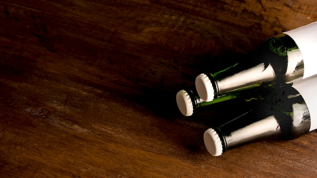 Verdes botellas de cerveza en la mesa de madera