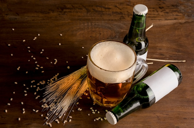 Verdes botellas de cerveza con vaso de cerveza en la mesa de madera