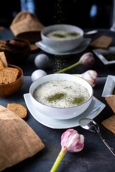 Verdes dovga sopa ligera blanca con diferentes hierbas en gris