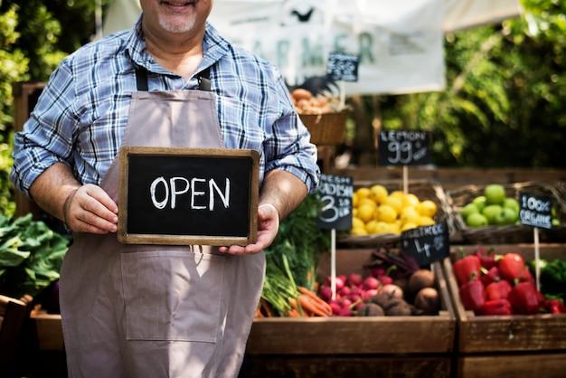 Verdulero que vende productos agrícolas frescos orgánicos en el mercado agrícola