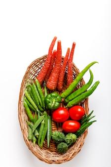 Verdura cruda en cesta de madera