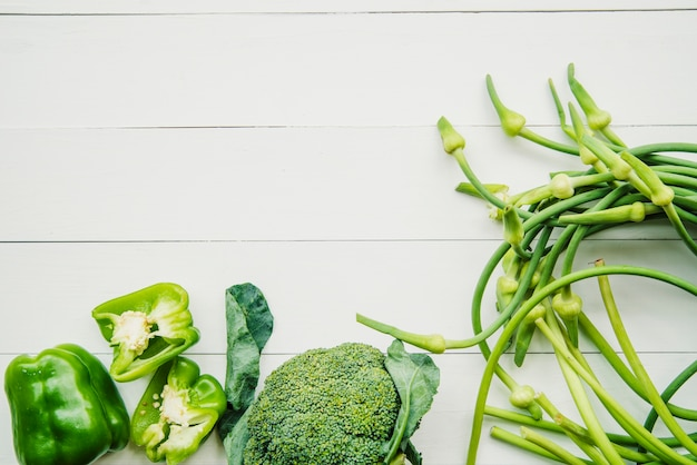 Verdura verde en mesa de madera blanca